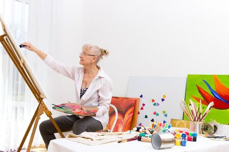 An elderly woman is sitting in front of an easel in her studio