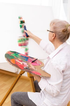 Older woman sitting in front of an easel and painting a picture