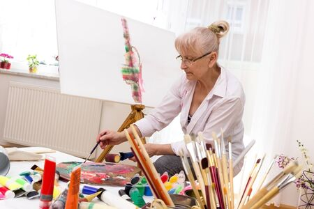 Pensioner mixing different colors for her picture
