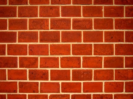 The picture represents a close-up details of a wall with reddish bricks.