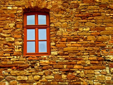 embed: An old brick wall  with a red window
