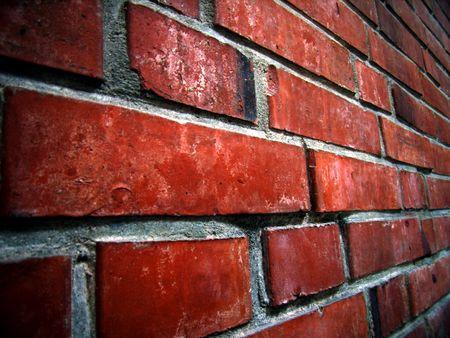 periferia: Un muro di mattoni-rossastro con close-up dettagli.