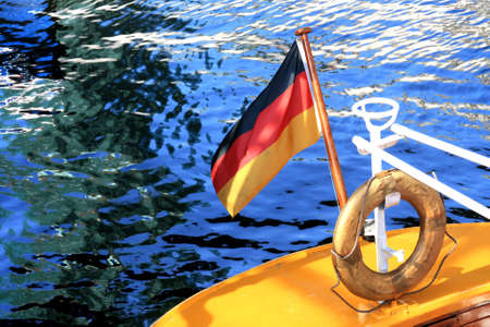 The picture shows the stern of a yellow sailboat with a German flag and the safety ring in Hamburg harbour. photo