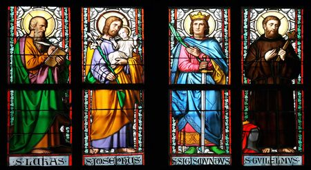 Stained glass window in St.Vitus cathedral, Prague, depicting St. Lukas, St.Josephus, St.Sigismundus and St. Guilelmus. photo