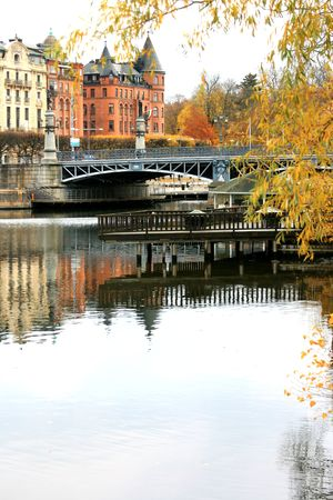 Djurgardsbro in autumn reflected on water (Stockholm, Sweden). photo
