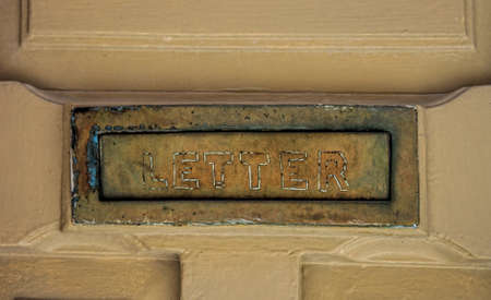 Close-up details of an aged letter post sign on a door.