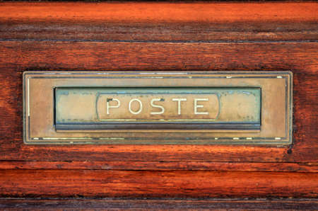 Close-up details of an aged post sign on a door.