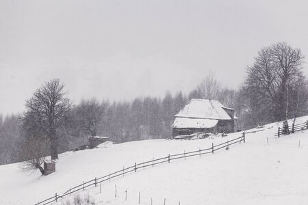 Traditional household in the Romanian Carpathians during a snowstorm