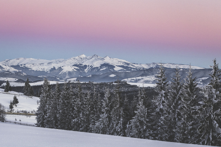 Rosu, Ineut and Ineu (from right to left) peaks viewed from Tihuta Pass, along with the Belt of Venus and Earths shadow Stock Photo