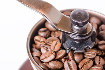 Manual coffee grinder with coffee beans. Isolated. White background. Modern style. Roasted coffee beans