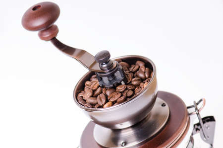 coffee grinder: Manual coffee grinder with coffee beans. Isolated. White background. Modern style. Roasted coffee beans