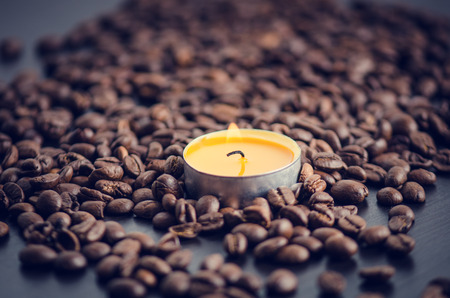 grained: Coffee beans on a black background with candle. Raw coffee beans and fire from candle. Grained product. Hot drink. close up