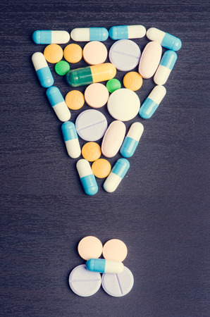 psychologists: Pharmacy background on a black table.Exclamation. Punctuation mark. Tablets on a black background. Pills. Medicine and Health. Close up of capsules. Differend kind of pills