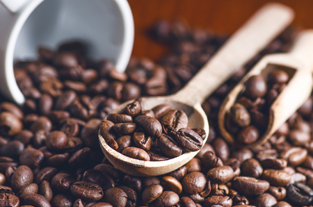 Spoon of coffee beans. Background. Energy. Raw coffee beans. Grained product. Hot drink. Close up. Harvesting. Natural background. Lifestyle. Coffee break in a morning. Wooden spoon. Steam
