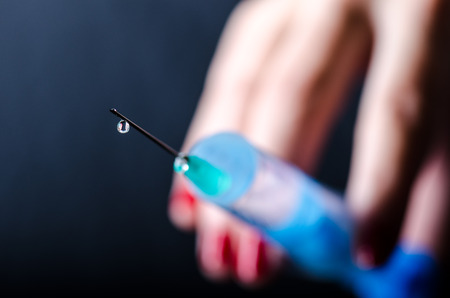 Medical injection on dark background. Medicine plastic vaccination equipment with needle. Health and care. Vaccination. Medicine background. Studio isolated. Phobia, Woman hand keep a injection