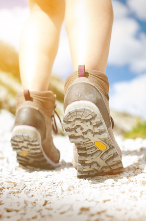 Woman hiker walk on a rocky ground. Sunny day.Trekking boots.Lens flare. Succesful backpacker. Stone. Step Stock Photo