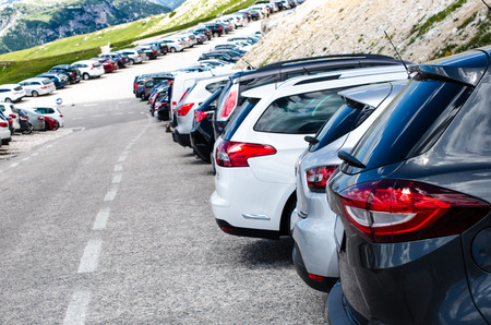 Cars in a parking lot in a middle of mountains. Vehicles on a beautiful sunshine. Transportation background