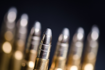 Ammunition on a dark blue background with reflection in a glass. Close up. Weapons. Bullets