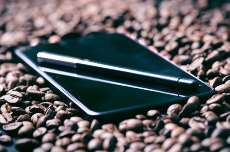 stylus pen: coffee beans. Stylus pen on a smart phone and raw coffee Background. Energy. Raw coffee beans. Harvesting. Natural background. Lifestyle. Coffee break in a morning. Mobile. Technology