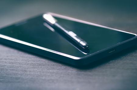 stylus pen: Stylus pen on a smart phone. Dark background. Technology mobile. Stock Photo