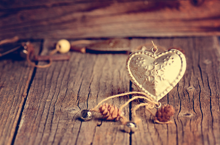 Silver heart on a wooden table with decorations. Valentines day. Love. Gift on a natural background. Candle and fire like a background