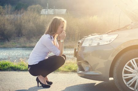 unfortunate: Woman crouching on the road next to a red warning triangle. Sad person. Damaged car. Natural background. Car accident.