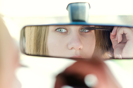 Woman putting make up in a car. Pretty young woman looking in mirror. Dangerous situation Stock Photo
