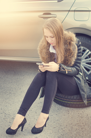 reckless: The girl wondered. Broken car on a background. Woman sit on a wheel. Sexy young woman repair a car. Natural background. Car accident.