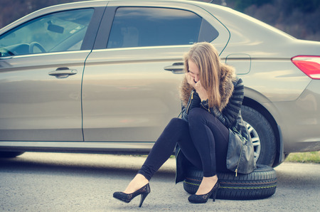 The girl wondered. Broken car on a background. Woman sit on a wheel. Sexy young woman repair a car. Natural background. Car accident.