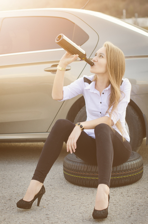 Drunk woman sit on a wheel by car. Woman drink a alcohol. Sexy young woman. Repair a car. Car accident. Stock Photo
