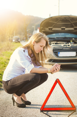 Woman crouching on the road next to a red warning triangle. Sad person. Damaged car. Natural background. Car accident.
