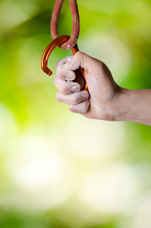 Man´s hand holding a carabine on a rope. Climbing equipment on a natural background. Hand in powder chalk magnesium.