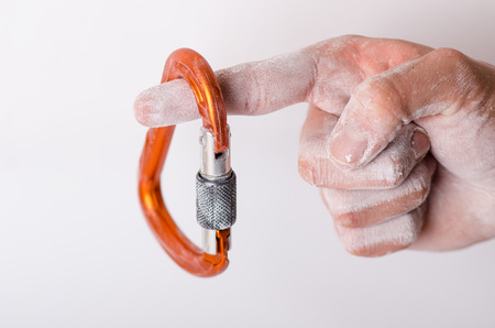 Man´s hand holding a carabine on a rope. Climbing equipment isolated on a white background. Hand in powder chalk magnesium.
