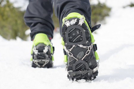 Hiking boots with equipment for ice. Snow like a background and sun. Sun is shining. Moutains and travel. Фото со стока