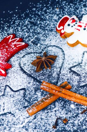 Christmas background decoration. Cinnamon, cookies shape such as heart and star. Flour and spices for a christmas baking on a dark background. Stock Photo