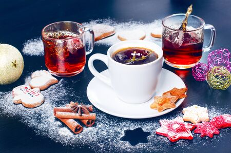 Coffee splash. Cup of coffee and tea with christmas cookies, decoration, sugar, cinnamon. Flour and spices for a christmas baking on a dark background.