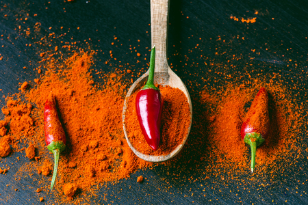 capsaicin: Red chilly peppers, spicy on a wooden spoon. Chilly on a wooden spoon. Vegetable. Concept of hot food.