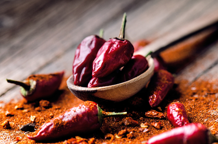 capsaicin: Red chilli peppers, spicy on a wooden spoon. Vegetable on a dark, wooden table. Concept of hot food.