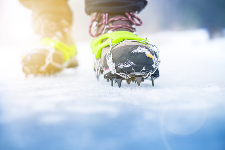 Hiking boots with equipment for ice. Snow like a background and sun. Sun is shining. Moutains and travel. Stock Photo