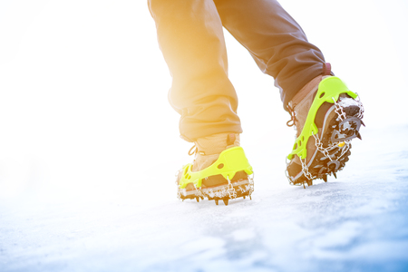 traction: Hiking boots with equipment for ice. Snow like a background and sun. Sun is shining. Moutains and travel. Stock Photo