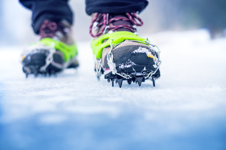 crampon: Hiking boots with equipment for ice. Snow like a background and sun. Sun is shining. Moutains and travel. Stock Photo