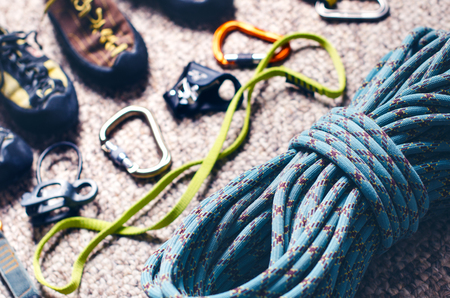 Climbing and mountaineering equipment on a carpet. Shoes, carbine, rope, lope, ascend-er. Concept of outdoor and extreme sport. Stock Photo