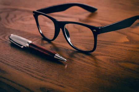 Glasses and pen on a wooden natural table. Office. Concept of work in a office and accessories.