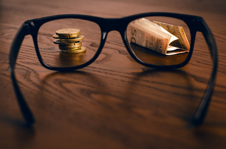 fixate: Euro money coins and paper money focused in glasses on a wooden table. Finance and office concept. Focused on money. Economy. Business background Stock Photo