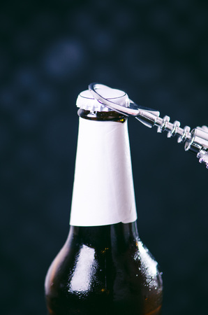 bottle opener: Glass bottle of cold beer and iron opener on a dark background. Hand opening a bottle. Alcohol and drinks concept.