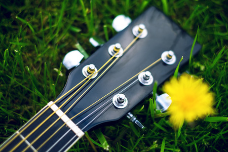 Detail of acoustic guitar on a grass. Natural background with flowers, grass and sun. Musical instrument