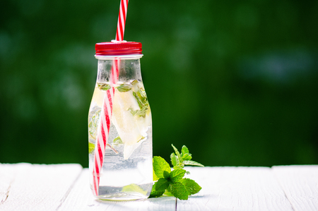 Refreshing homemade flavored water with lemon, lime and mentha on a white table in garden. Summer time. Beverages. Stock Photo