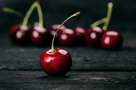 Cherries on a black table.. Natural wooden burnt table. Fresh food concept. Fruit. Summer time