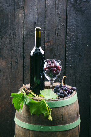 Glass and bottle of wine on a wooden barrel. Burnt, black wooden background. Vintage. Copyspace for a text. Grapes and green vine.