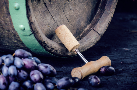 Corkscrew next to a wooden wine barrel. Wine on a wooden barrel. Burnt, black wooden background. Vintage. Copyspace for a text. Grapes and green vine.